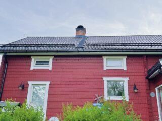 Vi kom hem till huset fullt av bin. Bilden visar ett rött hus med en skorsten där en bisvärm försökte bygga nytt bo.
