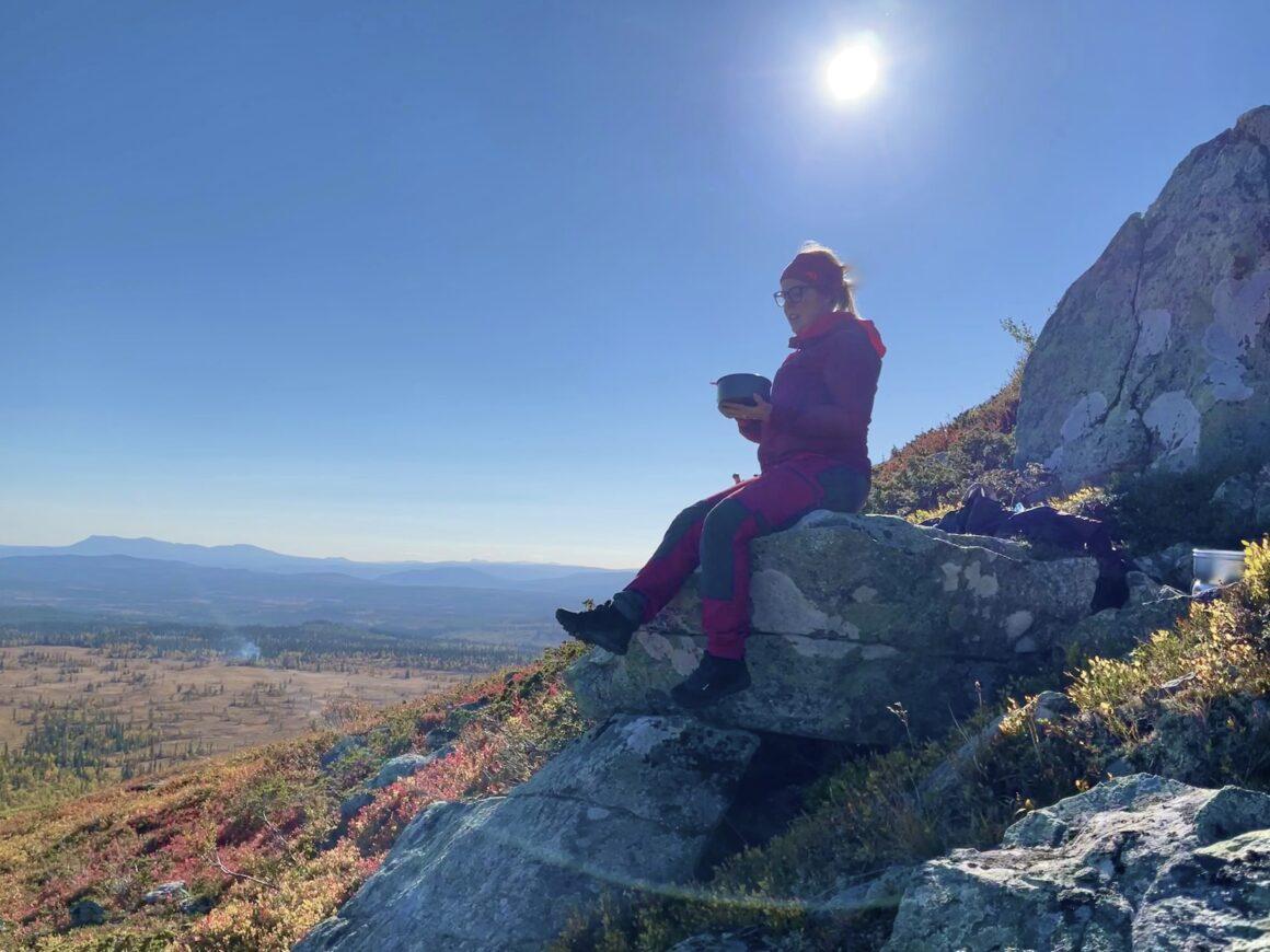 En glad tjej sitter på en stenbumling halvvägs upp på berget och äter sin lunch. Det är soligt och fint och magiskt utsikt från Särvfjället i Härjedalen.